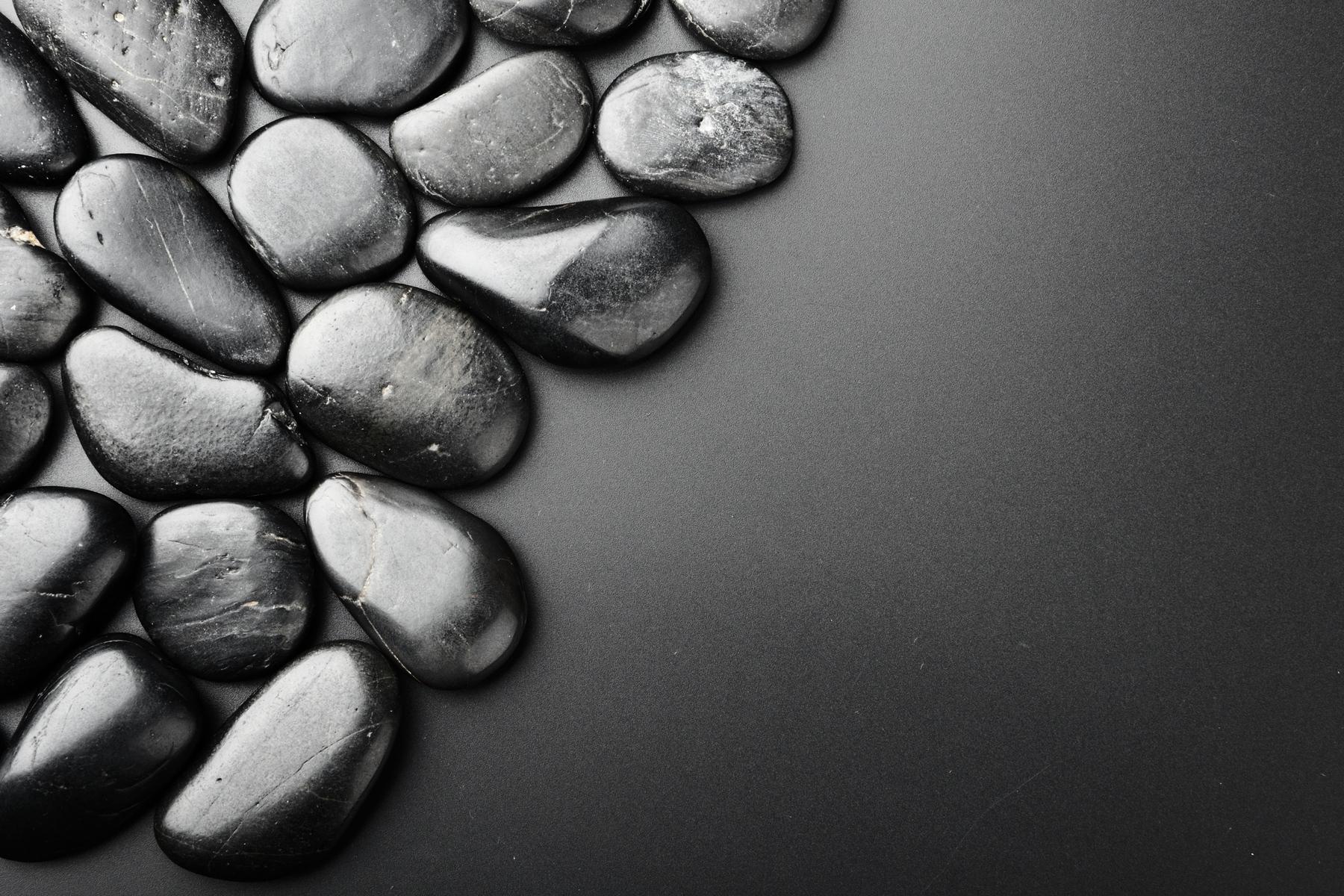 Galets noirs brillants sur fond gris foncé